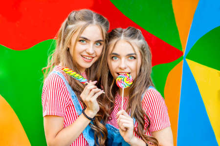 Beautiful teenage twin sisters in colorful clothes with lollipops caramel on colorful graffiti background