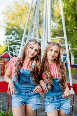 Beautiful twin sisters in colorful clothes and denim overalls on colorful swing background Stock Photo