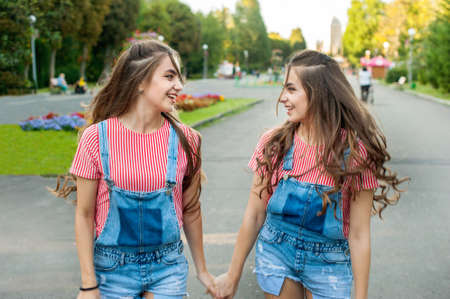 girls twins run on the background of attractions, emotions of happiness and joy, youth