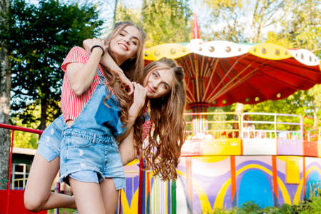 twin sisters in colorful clothes embracing, happy emotions, with colorful swings on background