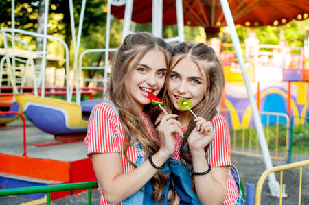Beautiful teenage twin sisters in colorful clothes with caramel lollipops on a background of colorful swings