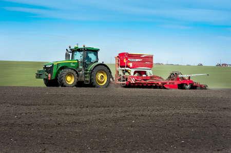 BAYKIVTSI, TERNOPOL REGION, UKRAINE - APRIL 10, 2021: Farmers sow, apply fertilizers using a John Deere 8370R tractor with a POTTINGER TERRASEM c8 seeder in a plowed field, sowing in Ukraine Redakční