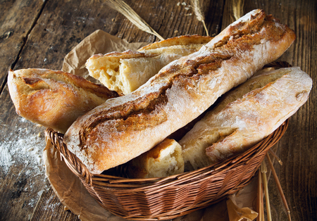 french bakery: Fresh baked bread on wood background