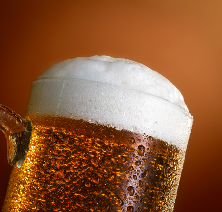 cold beer: Mug of cold light beer on brown background Stock Photo