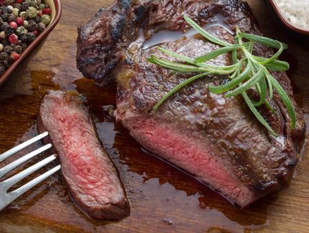 steak beef: medium roast rib-eye steak on wooden plate with pepper and salt