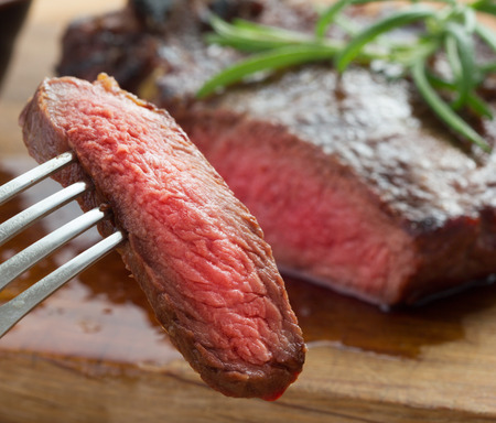 fillets: medium roast rib-eye steak on wooden plate with pepper and salt