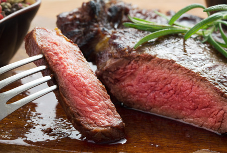 steaks: medium roast rib-eye steak on wooden plate with pepper and salt