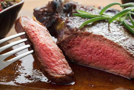 steak plate: medium roast rib-eye steak on wooden plate with pepper and salt