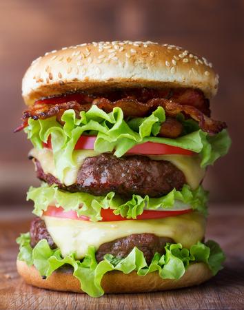 HAMBURGUESA: gran hamburguesa fresca con queso y tocino en la mesa de madera