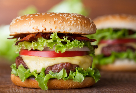 american food: fresh burger with cheese and bacon on wooden table Stock Photo