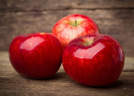 manzana roja: tres manzanas maduras rojas en fondo de madera