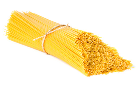 raw gold: stack of raw spaghetti isolated on white background Stock Photo