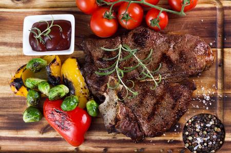porterhouse: big porterhouse grilled steak with vegetables on wooden plate Stock Photo