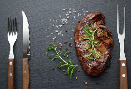 the medium: medium roasted steak with pepper and salt on slate plate