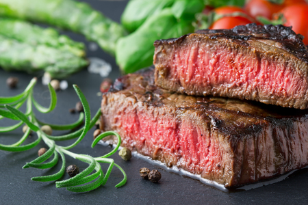 esparragos: filete asado medio con espárragos y tomates en la placa de pizarra