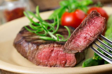 fillet steak: medium roasted steak with asparagus and tomatoes on plate