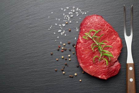 salt and pepper: raw steak with salt and pepper on slate plate Stock Photo