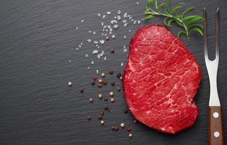 raw steak: raw steak with salt and pepper on slate plate Stock Photo