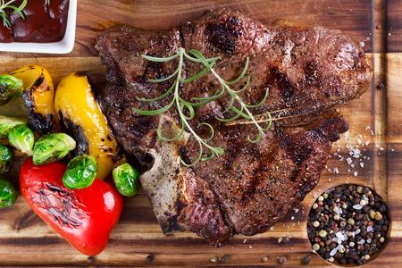 porterhouse: great porterhouse grilled steak with vegetables on wooden plate