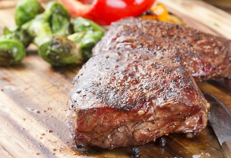 juicy: cut steak with vegetables on wooden desk Stock Photo