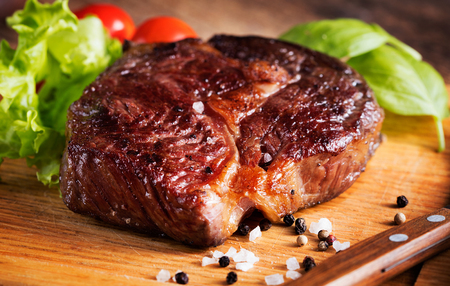 fried food: grilled rib-eye steak with herbs on wooden background