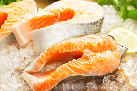 closeup view: close-up view of salmon steaks on ice with greens and lemon