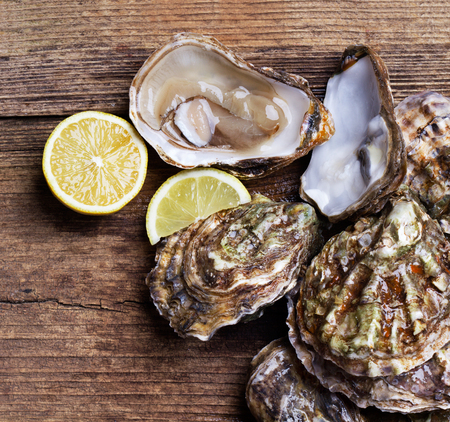 ste of fresh oysters with lemon slices on wooden background