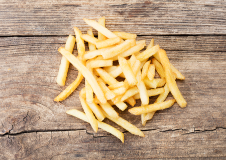 close-up view of heap of french fries on wooden background