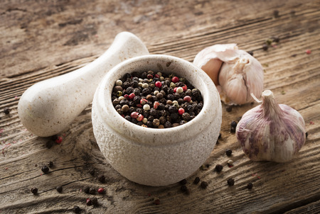mixed peppercorns in stone bowl on wooden background 스톡 콘텐츠
