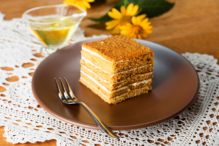 slice of traditional layered honey cake on brown plate