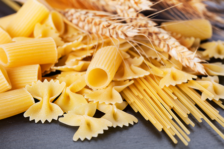 various pasta with ears of wheat on slate background