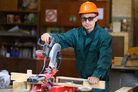 A young and handsome worker man in a helmet and glasses works at the machine