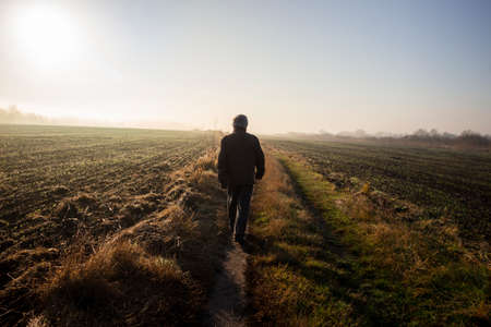 A man is walking on a country road