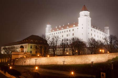bratislava: illuminated bratislava castle in the autumn fog