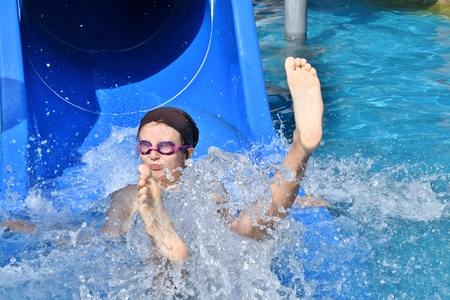Little girl sliding in the water slide during vacation in sommer