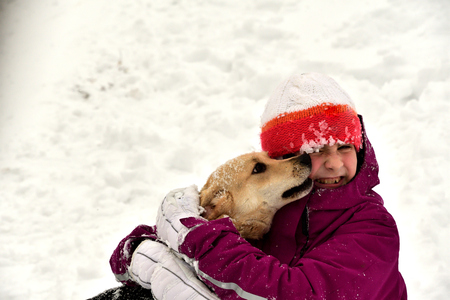 The dog jumps for joy at the girl and licks her face