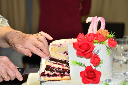 Grandma  cut with a knife with sweet cake to celebrate 版權商用圖片