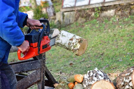 Traditional way of sawing wood wood with chainsaw in the village Banque d'images