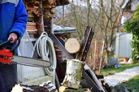 Sawing wood with chainsaw with safety glasses and helmet in the garden village Stock Photo