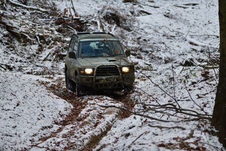 Off-road car rides down hill on snow and mud in forest