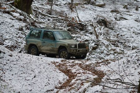 Dirty off-road car in forest on snow and mud Stock fotó
