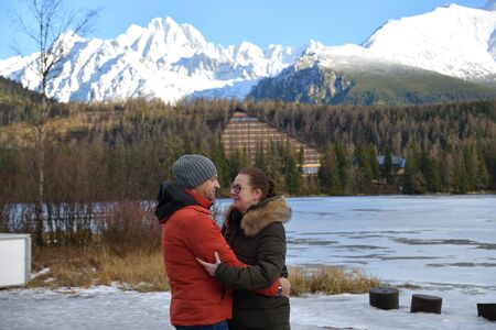 Two young people fallen in a love hug at a lake under the high mountains High Tatras Slovakia Stock Photo