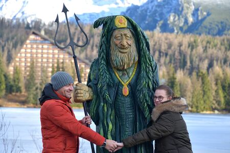 Woman and man fallen in love holding hands in embrace of wooden statue in High Tatras Slovakia
