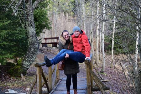 Loving man and woman standing in embrace on a wooden bench at the lake
