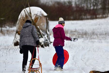 Mom and daughter are pulling sledge up the hill in the winter in the snow and around them is playing their pet dog