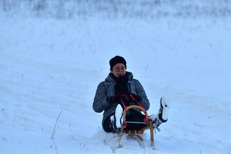 Woman sledding downhill on snow in winter and laughing with domestic cat in her arms Banco de Imagens