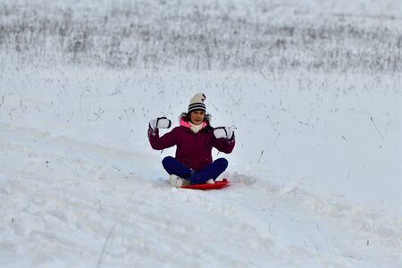 Girl sledding downhill on snow in winter and laughing with joy