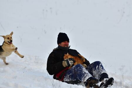Grandfather slide in the snow in his arms with a cat and a dog runs after them