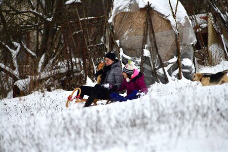 Mom and daughter slide in the snow along with a cat and a dog runs after them