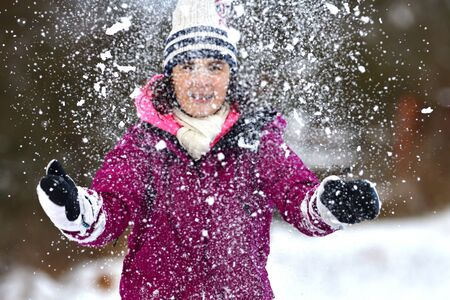 Girl enjoy the snow in winter and stretches her hands while snowing